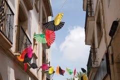 Kleurrijke die ventilators boven smalle straat worden vastgebonden Royalty-vrije Stock Afbeelding