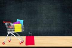 Kleurrijke document het winkelen zakken in karretje op houten lijst met zwarte Stock Fotografie