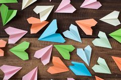 Kleurrijke document vliegtuigen op houten lijstachtergrond Stock Foto's