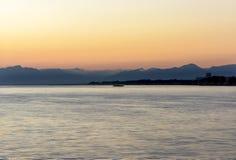 Kleurrijke donkere zonsondergang over het overzees en de bergen Stock Foto's