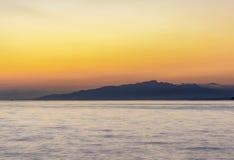Kleurrijke donkere zonsondergang over het overzees en de bergen Stock Afbeelding