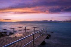Kleurrijke donkere zonsondergang over het overzees met een oude pijler op de voorgrond Stock Afbeelding