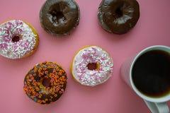 Kleurrijke donuts op een roze lijst die voor ontbijt met kokend hete koffie worden gediend stock afbeelding