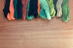 Kleurrijke draden op een houten achtergrond Stock Foto's