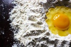 Kleurrijke eierdooier in de bloem op de lijst stock afbeeldingen