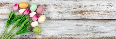 Kleurrijke eieren en tulpen voor Pasen-vakantie op rustiek wit hout Stock Afbeeldingen