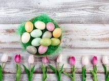Kleurrijke eieren en tulpen voor Pasen-vakantie op rustiek wit hout Royalty-vrije Stock Afbeelding