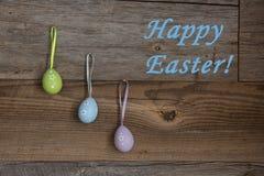 Kleurrijke eieren op doorstane houten muur met Gelukkige Pasen-groet Stock Fotografie