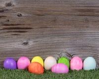 Kleurrijke eieren voor Pasen-vakantie die op gras met plattelander rusten wo Royalty-vrije Stock Foto's