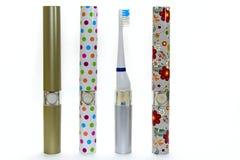 Kleurrijke elektrische die tandenborstel vier voor familie op witte achtergrond wordt geïsoleerd royalty-vrije stock afbeelding