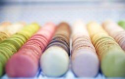 Kleurrijke enigszins ronde snoepjes macarons in een doos op de showcase van Th Stock Afbeelding