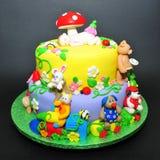 Kleurrijke fondantjecake met dierenbeeldjes stock foto's