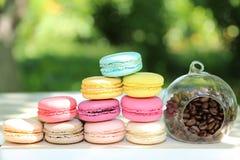 Kleurrijke Franse macarons met koffie op de aardachtergrond Stock Afbeeldingen