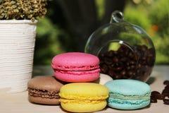 Kleurrijke Franse makarons met koffie op de aardachtergrond Royalty-vrije Stock Afbeelding