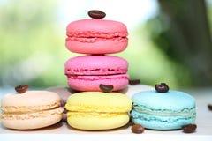 Kleurrijke Franse makarons met koffie op de aardachtergrond Stock Foto's