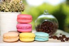 Kleurrijke Franse makarons met koffie op de aardachtergrond Stock Afbeelding