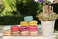Kleurrijke Franse makarons met koffie op de aardachtergrond Stock Foto