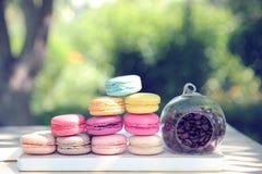 Kleurrijke Franse makarons met koffie op de aardachtergrond Royalty-vrije Stock Foto's