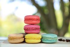 Kleurrijke Franse makarons met koffie op de aardachtergrond Stock Afbeeldingen