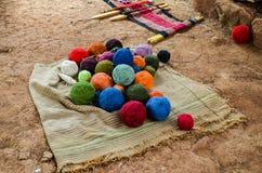 Kleurrijke garenballen op een gestreepte deken en een traditioneel om hand-wevend weefgetouw die worden gebruikt om doeken te mak Stock Foto's