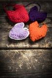 Kleurrijke gebreide harten op de donkere oude raad Stock Afbeeldingen