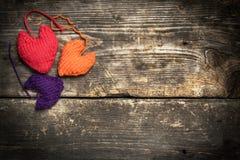 Kleurrijke gebreide harten op de donkere oude raad Royalty-vrije Stock Foto's