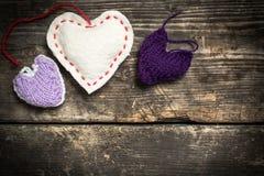 Kleurrijke gebreide harten op de donkere oude raad Stock Foto