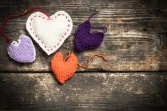 Kleurrijke gebreide harten op de donkere oude raad Royalty-vrije Stock Afbeelding