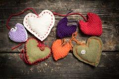 Kleurrijke gebreide harten op de donkere oude raad Royalty-vrije Stock Foto