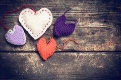 Kleurrijke gebreide harten op de donkere oude raad Stock Afbeelding