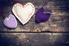 Kleurrijke gebreide harten op de donkere oude raad Stock Foto's