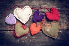 Kleurrijke gebreide harten op de donkere oude raad Stock Fotografie