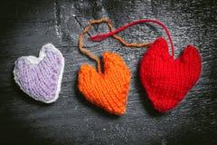 Kleurrijke gebreide harten op de donkere raad Stock Foto's