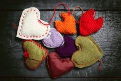 Kleurrijke gebreide harten op de donkere raad Royalty-vrije Stock Foto