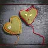 Kleurrijke gebreide harten op de donkere raad Stock Foto