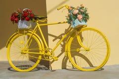 Kleurrijke geschilderde gele die fiets met bloemen wordt verfraaid Stock Foto's