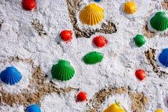 Kleurrijke geschilderde shells op witte muur Symbool van bedevaart Pelgrimsteken op de manier van Camino DE Santiago Het art stock afbeelding