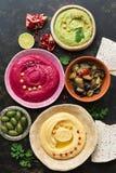 Kleurrijke gevarieerde hummus, caponata, olijven, pitabroodje en granaatappel op een donkere rustieke achtergrond De hoogste vlak stock foto