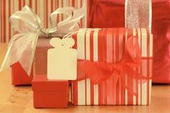 Kleurrijke gift in gestript verpakkend document, lege markering, en een klein rood vakje Stock Foto