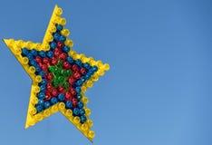 Kleurrijke glanzende ster van vele enige lampen met verschillende die kleuren op een markt, vóór een blauwe hemel wordt vrijgeste Stock Foto's