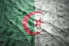 Kleurrijke golvende Algerijnse vlag op een achtergrond van het dollargeld Royalty-vrije Stock Afbeeldingen