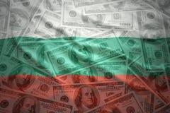 Kleurrijke golvende Bulgaarse vlag op een achtergrond van het dollargeld Royalty-vrije Stock Afbeelding