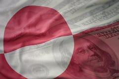 Kleurrijke golvende nationale vlag van Groenland op een Amerikaanse achtergrond van het dollargeld Stock Foto's