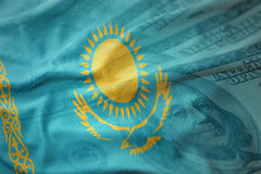 Kleurrijke golvende nationale vlag van Kazachstan op een Amerikaanse achtergrond van het dollargeld Royalty-vrije Stock Afbeelding
