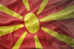 Kleurrijke golvende nationale vlag van Macedonië op een Amerikaanse achtergrond van het dollargeld Stock Fotografie