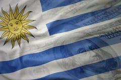 Kleurrijke golvende nationale vlag van Uruguay op een achtergrond van het dollargeld Het concept van financiën royalty-vrije stock afbeelding