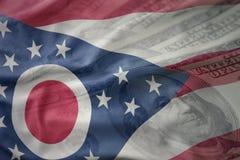 Kleurrijke golvende vlag van de staat van Ohio op een Amerikaanse achtergrond van het dollargeld stock foto
