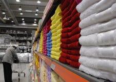 Kleurrijke handdoeken op plank in stor royalty-vrije stock afbeelding