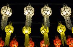 Kleurrijke hangende lantaarns die op nachthemel aansteken stock foto's