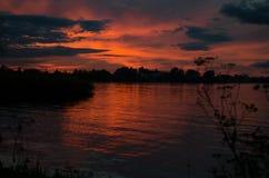 Kleurrijke hemel en kleurrijk water in meer dat in avond wordt weerspiegeld stock afbeeldingen